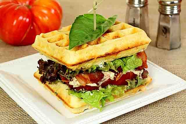 Cheesy Waffle BLT Sandwiches Served on a White Square Plate with a Basil Leaf Garnish