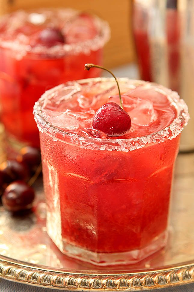 Cherry Old Fashioned Smash Cocktail on a Silver Tray with a Sugared Rim and a Whole Cherry with Stem for Garnish
