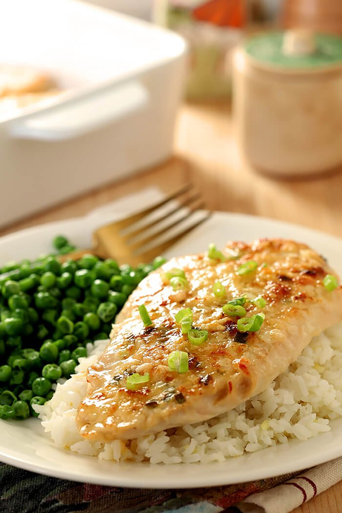 Serving of Broiled Chicken Parmesan on Rice with Green Peas