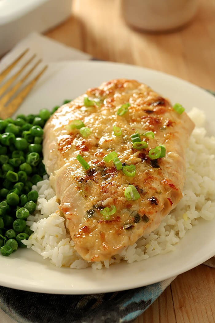Broiled Chicken Parmesan Closeup Served on a Bed of Rice with a Side of Green Peas