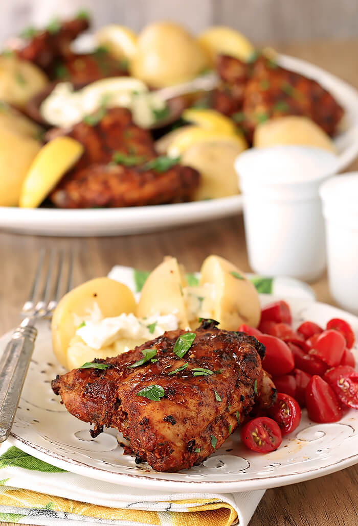 Spanish Tapas Chicken Thighs on Whilte Plate Served with Potatoes and Cherry Tomatoes