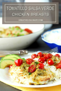 Tomatillo Salsa Verde Chicken Breasts on a White Plate with Avocado and Cherry Tomatoes