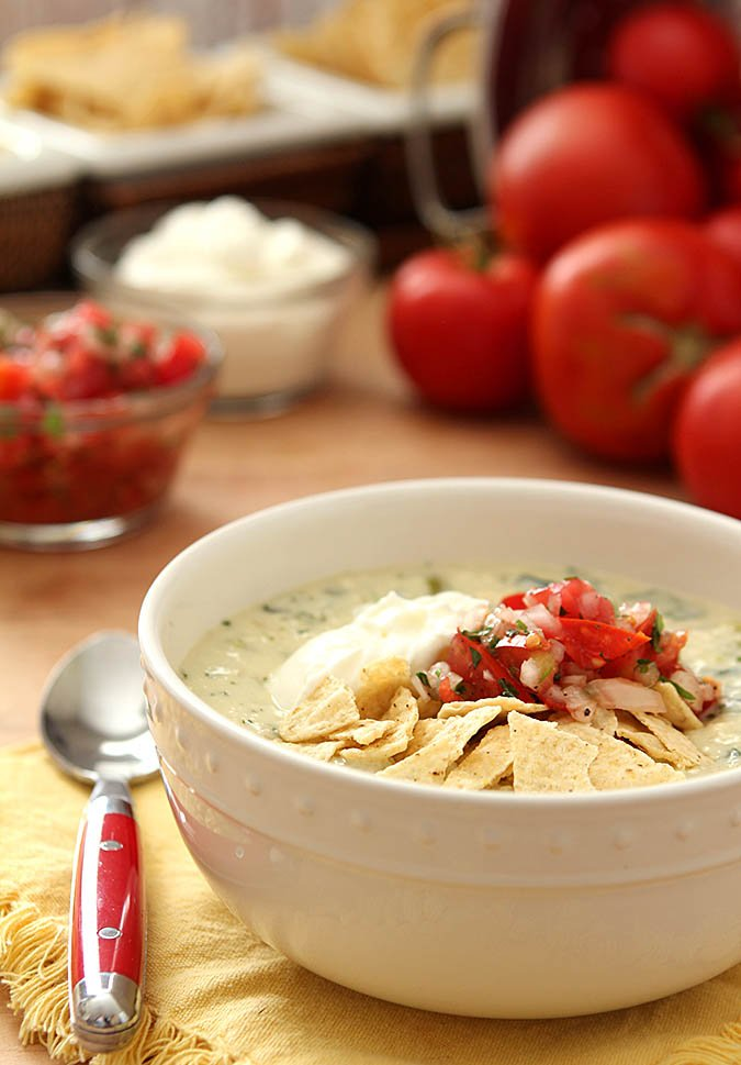 Chile Relleno Soup Served in a White Bowl and Garnished with Chips, Sour Cream, and Tomato Salsa
