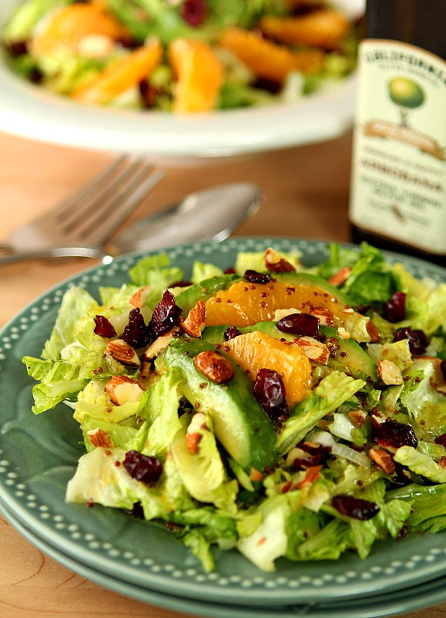 Chopped Salad with Avocado and Orange with an Orange Honey Mustard Dressing Served on a Green Plate