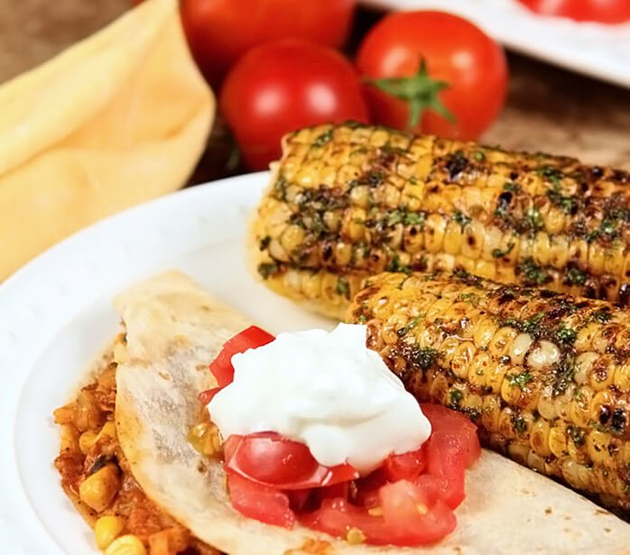 Cilantro, Honey, and Chile Corn on the Cob Served with a Warm Taco on a White Plate