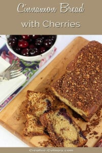 Cinnamon Bread with Cherries on a Bread Board with a Bowl of Fresh Cherries.
