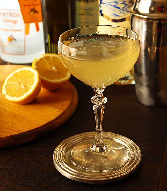 Corpse Reviver №2 in array with oranges and bottle of alcohol.