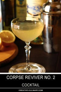 Corpse Reviver No 2 Cocktail in a Coupe Glass with Orange Halves in Background