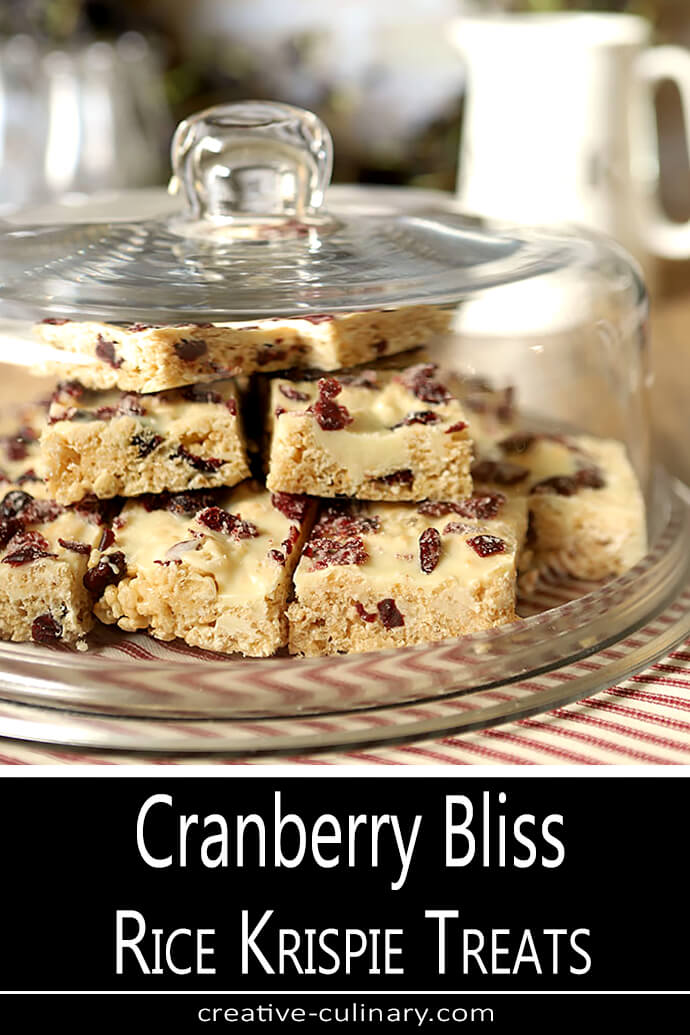 Cranberry Bliss Rice Krispie Treats Stacked on a Glass Bakery Plate with Glass Lid