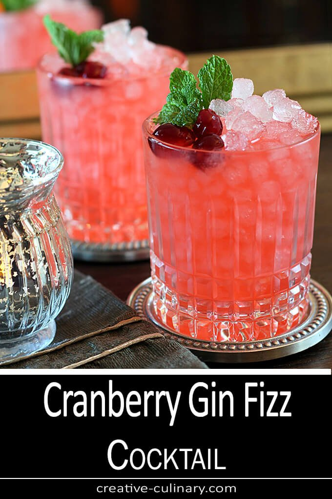 Cranberry Gin Fizz Cocktail garnished with mint and cranberries in a lowball glass.