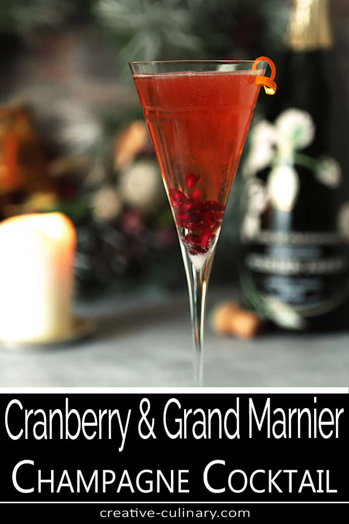Cranberry and Grand Marnier Champagne Cocktail Served in a Tall Champagne Glass with an Orange Twist