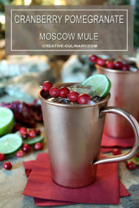 Cranberry Pomegranate Moscow Mule Served in a Copper Mug with Cranberry and Lime Garnish