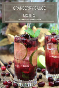 Cranberry Sauce Mojito Cocktails in a Tall Glass Garnished with Cranberries and Mint
