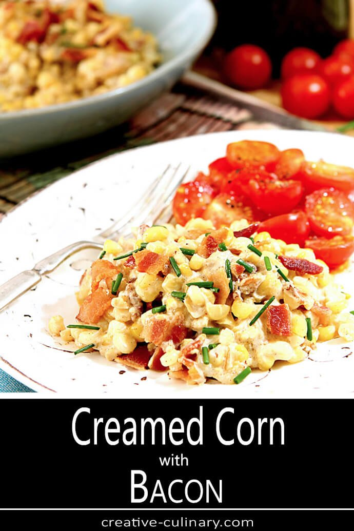 Creamed Corn with Bacon Served with Sliced Tomatoes on a White Plate