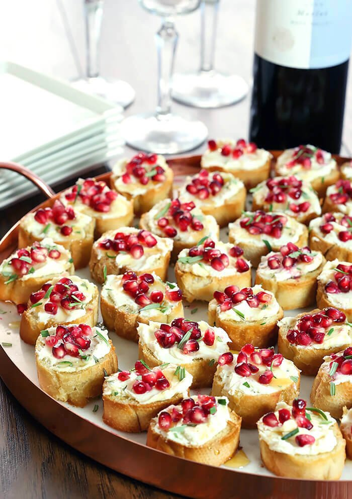 Crostini with Goat Cheese, Pomegranate Arils, and Rosemary Served on a Platter with Copper Edge