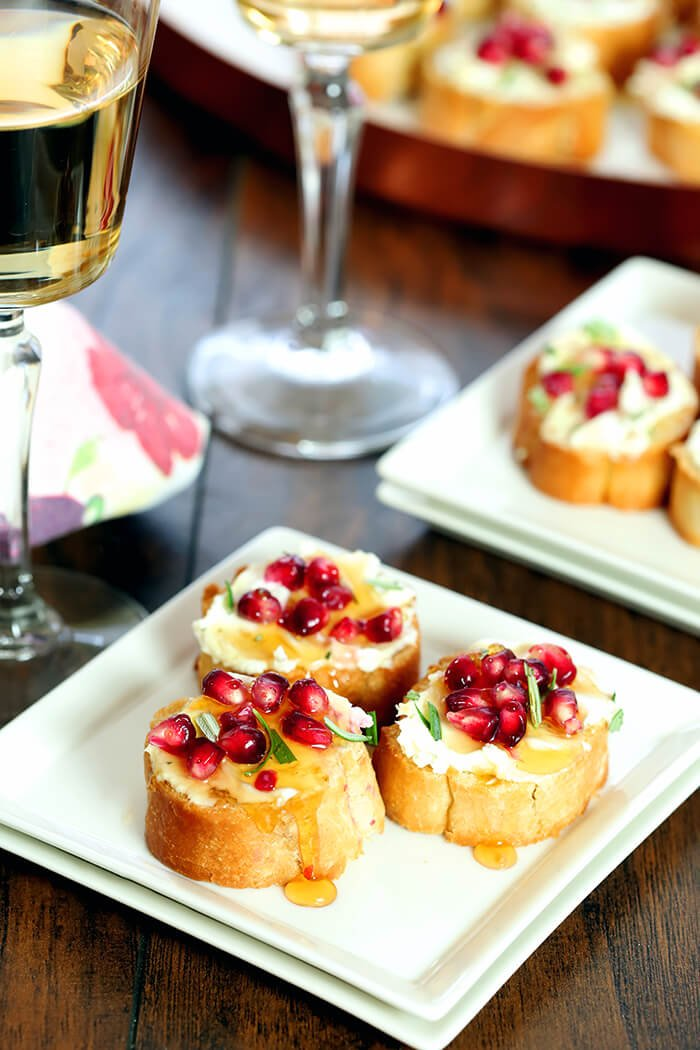 Crostini with Goat Cheese, Pomegranate Arils, and Rosemary Served on Square Plates with a Drizzle of Honey