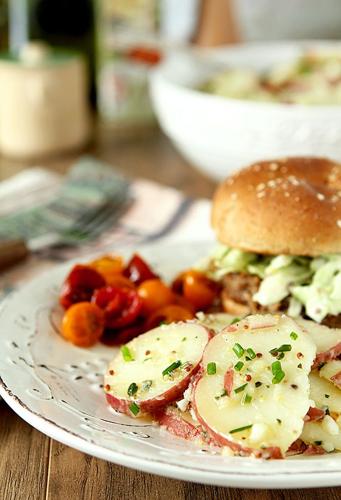 French Potato Salad with Herbs on a White Plate with a Sandwich and Chopped Tomatoes