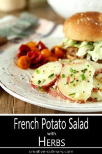 French Potato Salad with Herbs Served on a White Plate with Pork Sandwich and Cherry Tomatoes