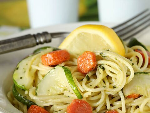 Garlic Pesto Pasta with Carrots and Zucchini Served with a Lemon Wedge in a White Bowl