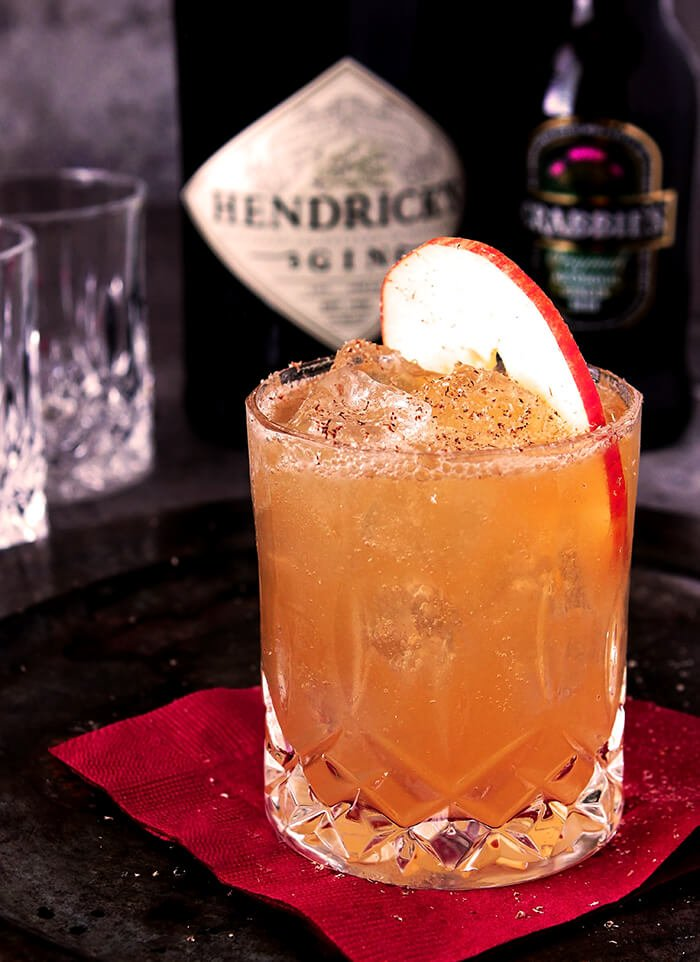 Gin, Apple Cider, Lemon and Ginger Beer Cocktail in a Highball Glass Garnished with an Apple Slice and Nutmeg
