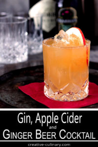 Gin, Apple Cider, Lemon and Ginger Beer Cocktail in a Highball Glass Garnished with an Apple Slice
