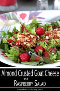 Warm Goat Cheese crusted with Almonds added to Raspberries for a Salad; all Served on a White Plate