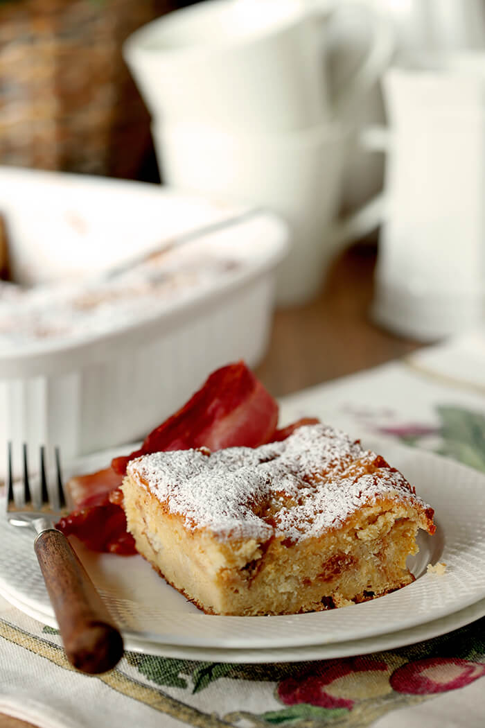 Gooey Butter Cake Overnight French Toast on a White Plate with Bacon on the Side.