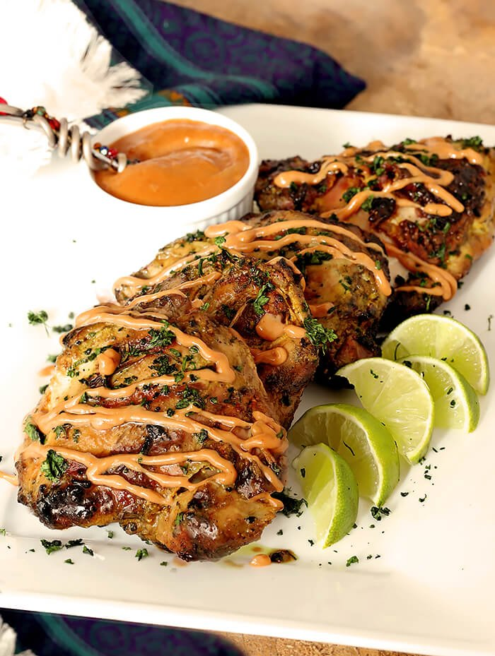 Grilled Chicken Satay with Peanut Sauce on Serving Plate with Lime Wedges