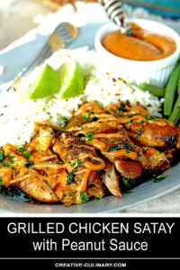 Grilled Chicken Thighs with Peanut Sauce on Plate with Rice Garnished with Lime Wedges