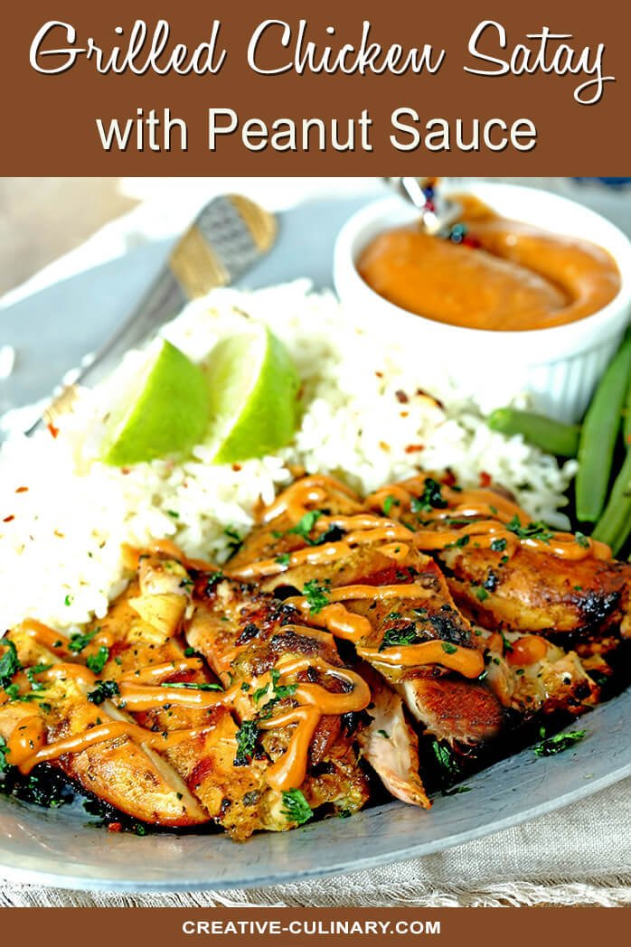 Grilled Chicken Satay with Peanut Sauce on Plate with Rice Garnished with Lime Wedges