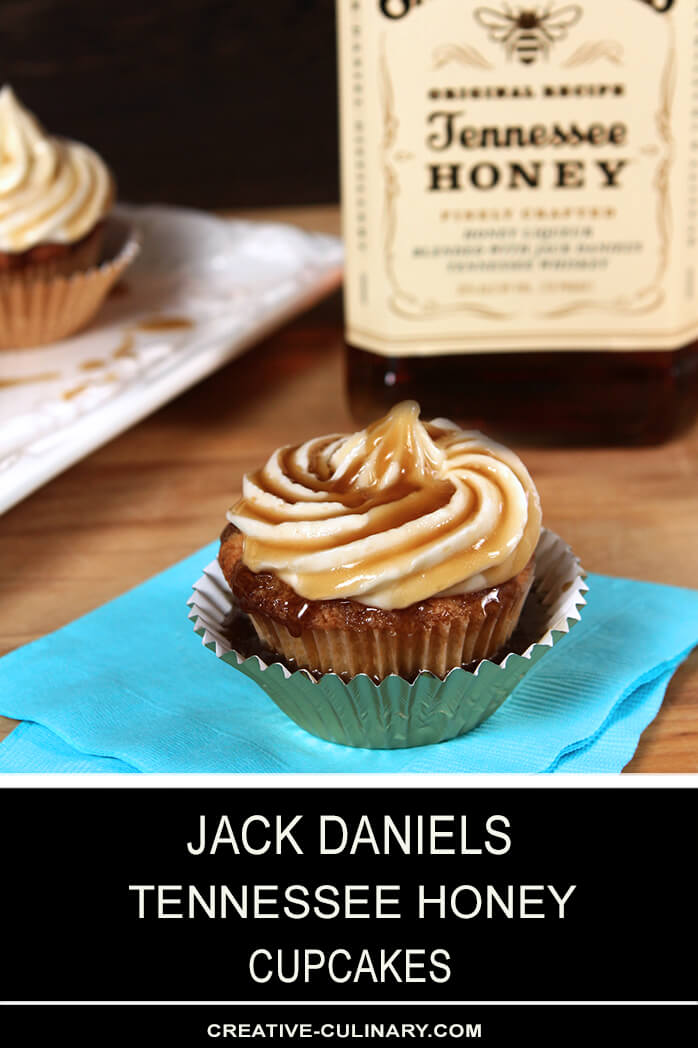 Closeup of Jack Daniels Honey Whiskey Cupcakes with a Boozy Drizzle from a Spoon In a Metallic Cupcake Liner in Front of a Bottle of Jack Daniels Tennessee Honey