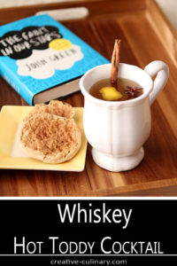 Whiskey Hot Toddy Cocktail Served in a White Mug on a Tray with Muffins and a Book