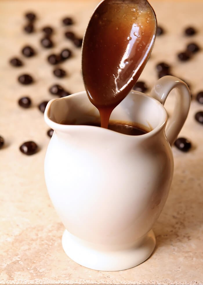 A Spoon Drizzling Irish Coffee Caramel Sauce into a White Ceramic Pitcher
