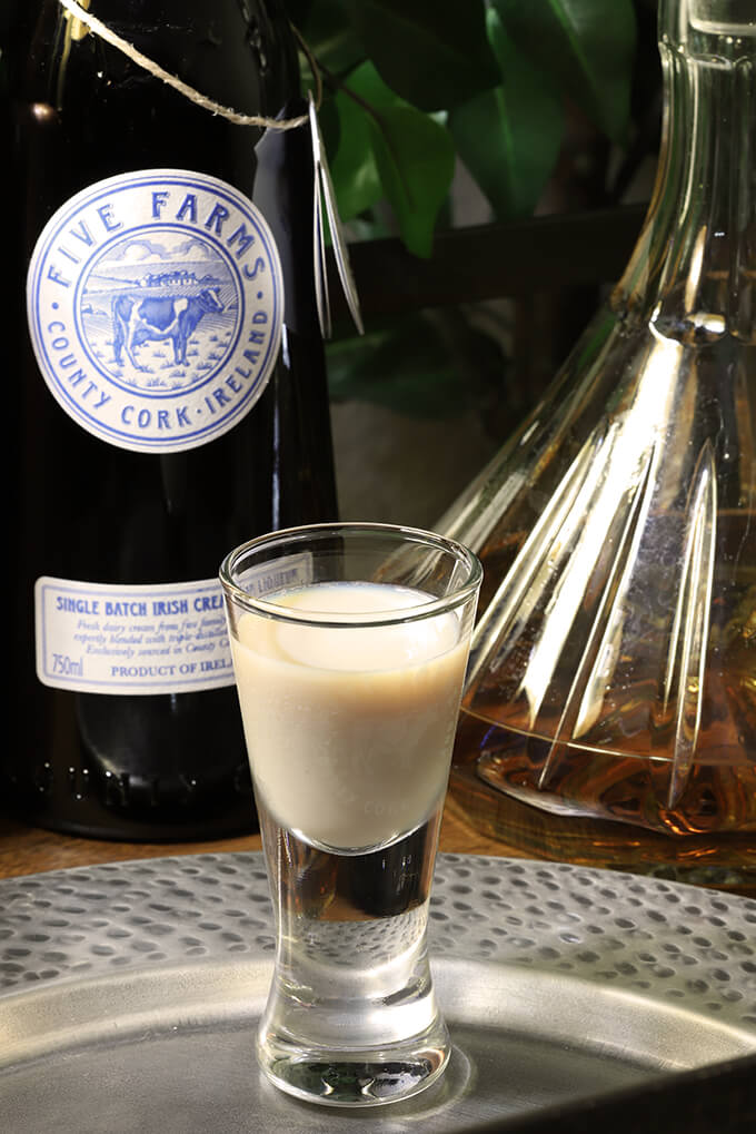 The Irish Toast Cocktail with Irish Whiskey and Five Farms Irish Cream with Bottles of Irish Cream and Irish Whiskey