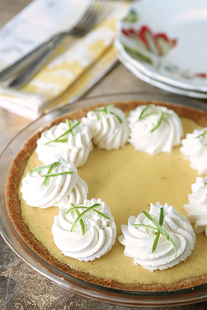 Key Lime Pie with Whipped Cream and Lime Zest in a Table Setting