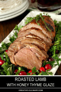 Roasted Lamb with Honey Thyme Glaze Carved and on a White Rectangular Serving Platter Garnished with Parsley and Cranberries
