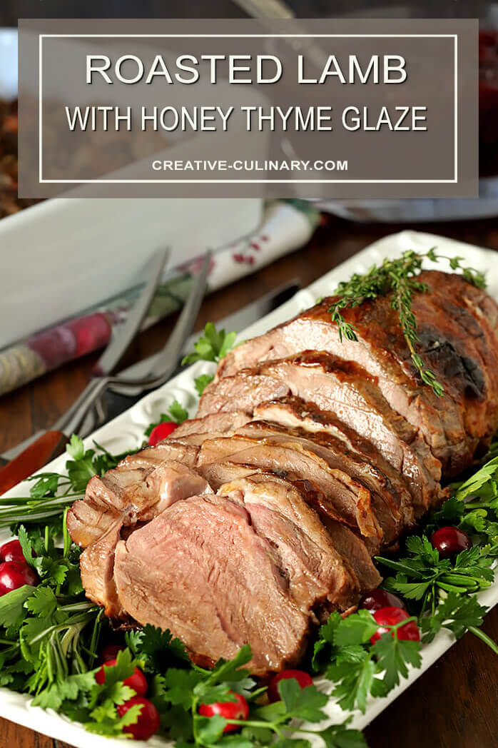 Roasted Lamb with Honey Thyme Glaze Sliced and on Serving Plater with Parsley and Cranberry Garnish