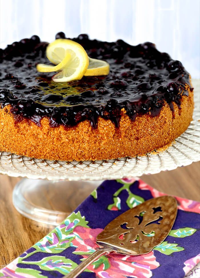 Whole Lemon Blueberry Cheescake with a Blueberry Topping with Lemon Garnish on a White Cakeplate