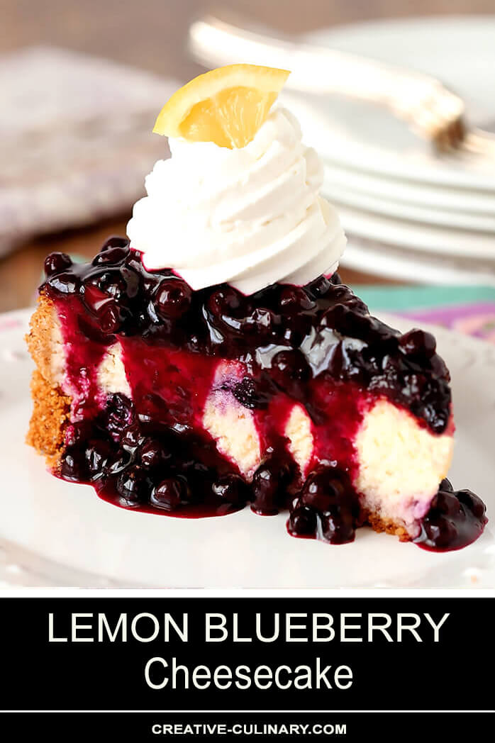 Single Slice of Lemon Blueberry Cheescake with a Blueberry Topping Served on a White Plate with Whipped Cream Topping