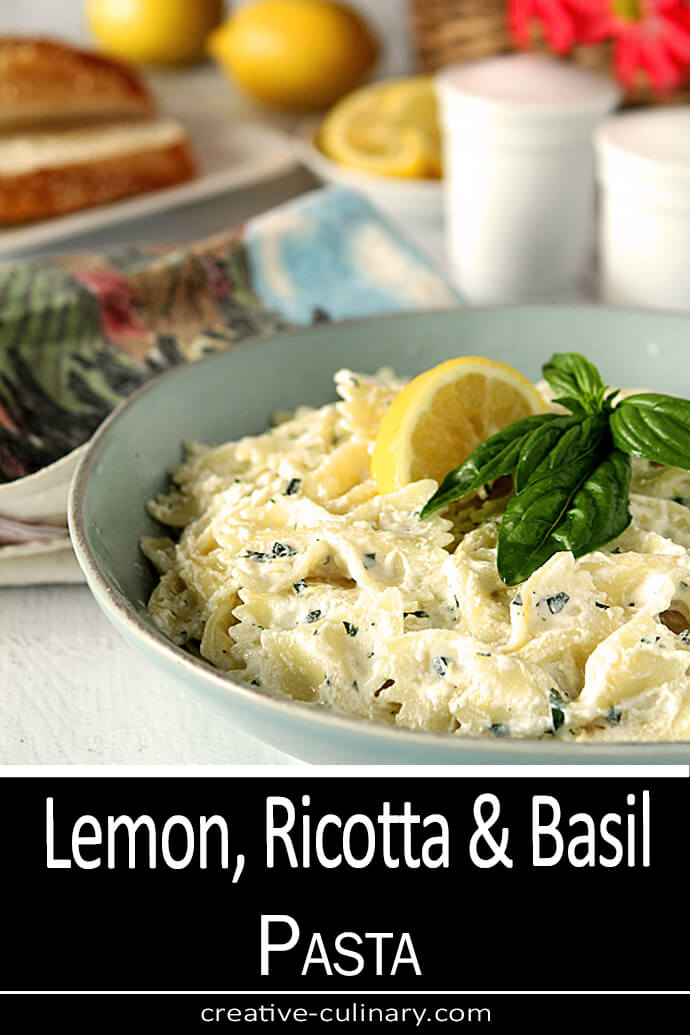 Lemon, Ricotta, and Basil Pasta Served in a Light Blue Stoneware Bowl with Basi and Lemon Garnish