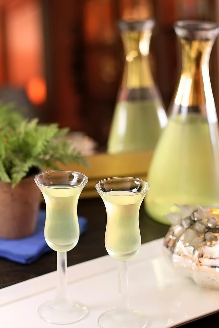 Homemade Limoncello Liqueur Shown with a Finished Bottle and Two Glasses of Chilled Liqueur