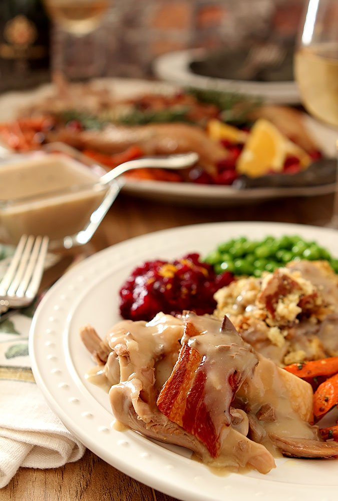 Maple Roasted Turkey with Sage and Bacon Served with Corned Bread Stuffing, Peas, and Cranberry Sauce on a White Plate
