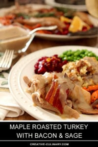 Maple Roasted Turkey with Bacon and Sage on Plate with Cranberry Sauce, Peas, and Dressing with Gravy