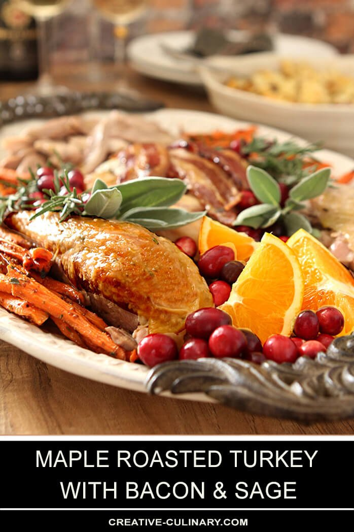 Maple Roasted Turkey with Bacon and Sage Served Cut into Pieces on Platter with Oranges and Carrots and Garnished with Sage