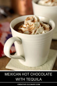 Mexican Hot Chocolate with Tequila Served in a White Mug with Whipped Cream on Top and Dusted with Cinnamon