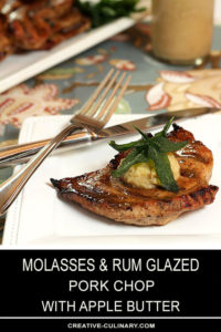 Molasses and Rum Pork Steaks with Apple Butter Served on a Square Plate and Garnished with Sage Leaves