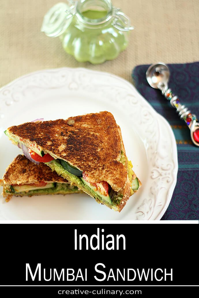 Mumbai Sandwich with fresh veggies is cut in half and served on a white plate.