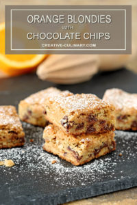 Chocolate Chip Blondies with Orange Zest Stacked and Dusted with Powdered Sugar