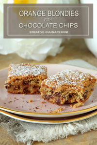 Chocolate Chip Blondies with Orange Zest on Pink Plate and Dusted with Powdered Sugar