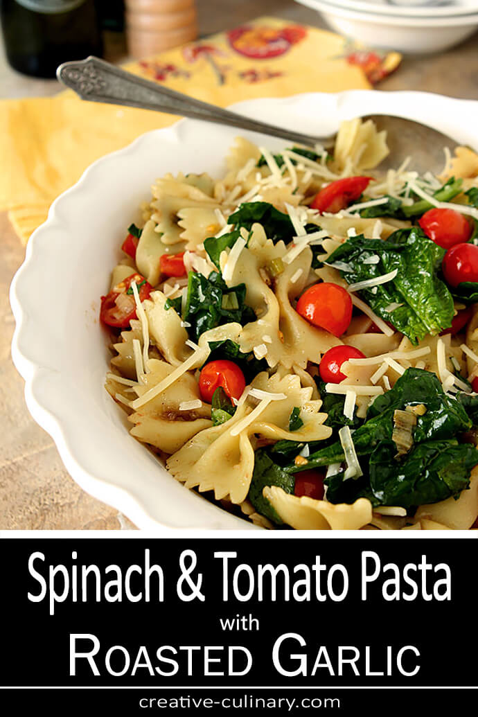 Pasta with Spinach and Tomatoes Served in a Large White Bowl